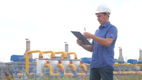 Teamwork gas production station concept. Engineering man standing writes documents on digital tablet white safety helmet stock video