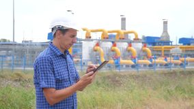 Teamwork gas production station concept. Engineering man standing writes documents on digital tablet white safety helmet stock footage