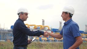 Teamwork gas production station concept. slow motion video. two engineers in helmets shaking hands on a gas supply. Business contract. two workers work at stock video