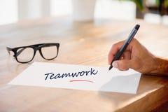 Teamwork gegen Seitenansicht der Handschrift auf weißer Seite auf Arbeitsschreibtisch Stockbilder