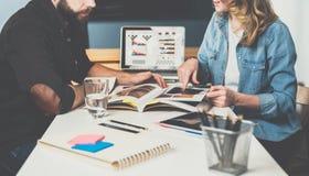 teamwork Geschäftsfrau und Geschäftsmann, die bei Tisch sitzen und Blick in den Journaldaten Auf Tabelle ist Tablet-Computer Lizenzfreie Stockfotografie