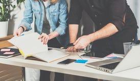 teamwork Geschäftsmann und Geschäftsfrau nahe Tabelle stehend und durch einen Ordner mit Dokumenten Blätter getrieben Lizenzfreie Stockfotografie