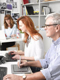 Teamwork in graphic design studio. Beautiful graphic designer sitting at desk and working together with colleagues. Small business royalty free stock image