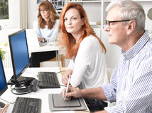 Teamwork in graphic design studio. Beautiful graphic designer women sitting at desk and working together with colleagues. Small business stock photo