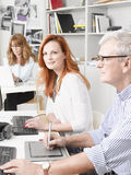 Teamwork in graphic design studio. Beautiful graphic designer women sitting at desk and working together with colleagues. Small business stock photography