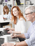 Teamwork in graphic design studio. Modern graphic designer women sitting at desk and working together with colleagues. Small business royalty free stock images