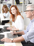 Teamwork in graphic design studio. Modern graphic designer women sitting at desk and working together with colleagues. Small business royalty free stock photo