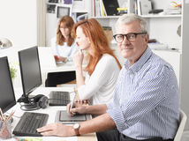 Teamwork in graphic design studio. Senior graphic designer sitting at desk and working together with colleagues. Small business royalty free stock images