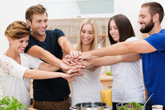 Teamwork. Group of enthusiastic multicultural young friends with happy smiles standing in the kitchen placing their hands in a stack denoting cooperation and Stock Photography