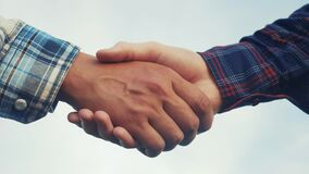 Teamwork handshake concept. two people shake hands shaking lifestyle hands. different skin colors shake hands conclude a