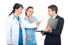 Teamwork having discussion and using laptop. Two doctors women having discussion with a businessman with laptop and pointing to object isolated on white Royalty Free Stock Photo