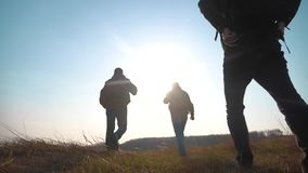 Teamwork help business travel silhouette concept. Group hikers of people slow motion video walking in a field on. Teamwork help business travel silhouette stock video footage