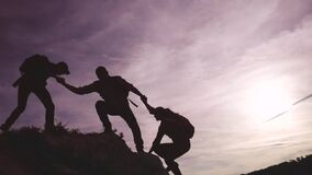 Teamwork help business travel silhouette concept. group team of lifestyle tourists lends a helping hand climb the cliffs