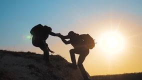 Teamwork help business travel silhouette concept. Group of tourists lends a helping hand climb the cliffs mountains. Teamwork help business travel silhouette stock footage