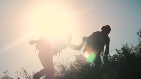 Teamwork help business travel silhouette slow motion video concept. Helping hand silhouette between two climbers stock video footage