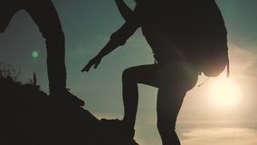Teamwork help business travel silhouette slow motion video concept. Helping hand silhouette between two climbers stock footage