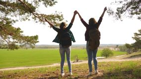 Teamwork Hiker Girls Raising Her Hands Up, Celebrating Victory And Enjoying Scenery. women on vacation travel through. Forest with backpack, raise their hands stock footage