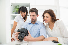 Teamwork holding digital camera and interacting. In the office Royalty Free Stock Image