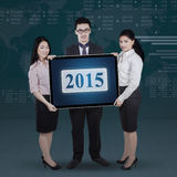 Teamwork holding number 2015 with financial background Stock Image