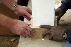 Teamwork in House Building. A pair of black hands and a pair of white hands working together on a home construction project Stock Photography