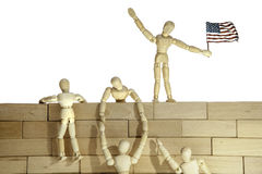 Teamwork or Illegal immigrants climbing a USA border wall. Model of anonymous people climbing a wall. One of the people holds the USA flag. Connotations are of royalty free stock photography