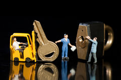 Teamwork Improving Security. A team of miniature model workmen offloading a key and padlock from a forklift to enhance security Stock Image