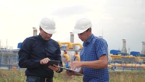 Teamwork. industry gas production station concept. slow motion video. two engineers in helmets are studying working with. A digital tablet in a factorygas stock video
