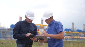 Teamwork. industry gas production station concept. Slow motion video. Two engineers in helmets are studying working with. A digital tablet in a factorygas stock video footage