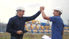 Teamwork. industry gas production station concept. slow motion video victory success. two engineers in helmets shaking. Hands on a gas supply business contract stock footage