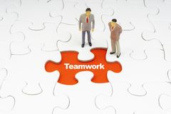 TEAMWORK inscription written on jigsaw puzzle and businessman miniature stock image