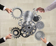 Teamwork and integration concept. Teamwork of businesspeople work together and combine pieces of gears to a mechanical system Stock Photos