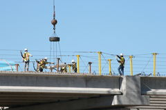 Teamwork: At Interstate 69 Construction Site, Laborers Work Together. Safety harnesses in place, a team of laborers guide a concrete section into place atop stock photos