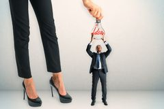 Teamwork and invention concept. Businesswoman hanging lamp to tiny businessman on concrete background. Teamwork and invention concept royalty free stock photos