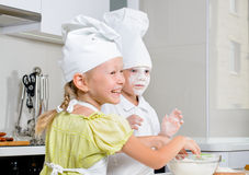 Teamwork in the kitchen. As a cute little boy and girl in chefs uniforms learning to bake roll out the dough and get flour ready to sprinkle on top Royalty Free Stock Image