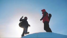 teamwork l'hiver de touristes de deux randonneurs a atteint le dessus des grimpeurs de touristes de montagne pour s'élever jusqu' banque de vidéos