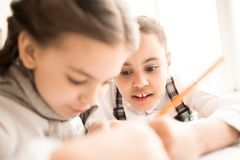 Teamwork at lesson. Little girl helping her friend during a lesson at school Royalty Free Stock Image