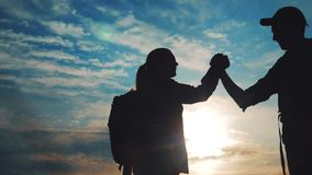 Teamwork lifestyle business journey concept win. Team tourists man and woman sunset silhouette help shake hands success. Victory. Slow motion video. Tourism stock video