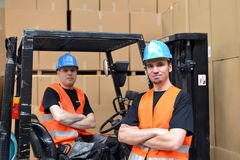 Teamwork in logistics - group of workers in a department store w. Ith forklift trucks and goods Stock Image
