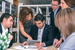 Teamwork looking business document in electronic tablet royalty free stock photos