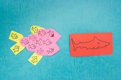 Teamwork. Lots of goldfish teaming together to take on a bigger goldfish Royalty Free Stock Image