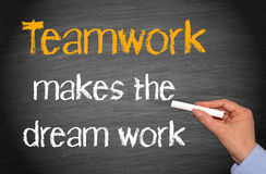 Teamwork makes the dream work. Female hand with chalk and text on chalkboard or blackboard background Stock Photo