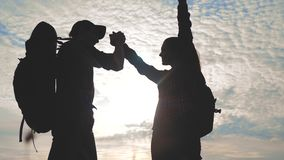 Teamwork man and woman business journey concept win. team tourists man and woman sunset silhouette help shake hands. Success victory. slow motion video. tourism stock video