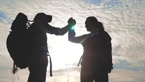 Teamwork man and woman business journey concept win. Team tourists man and woman sunset silhouette help shake hands. Success victory. Slow motion video. Tourism stock footage