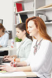 Teamwork at modern graphic design studio. Modern graphic designer women working with colleagues in office. Small business royalty free stock image