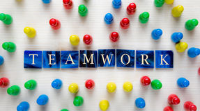 Teamwork. Mosaic tiles with letters and board game pieces - Concept of teamwork Royalty Free Stock Photography