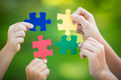 Teamwork. Multicolor puzzles in hands against green spring blurred background. Teamwork and solution concept Stock Image