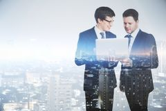 Teamwork and network concept. Businessmen using laptop together on abstract city background. Teamwork and network concept. Double exposure Stock Photos