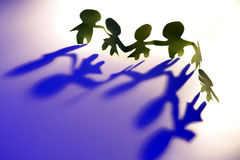 Teamwork Network Connectivity. A line of connected paper people, symbolizing teamwork, cooperation, networking, communication or connectivity royalty free stock images