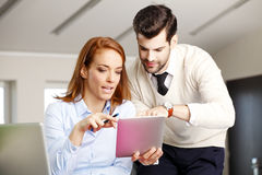 Teamwork at office. Executive business women giving advice young sales man, while working on digital tablet at office. Teamwork Royalty Free Stock Images