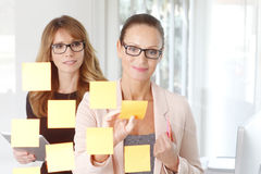 Teamwork at office. Portrait of two businesswoman working on new strategy while standing in front of transparent idea board and writing to post-it Royalty Free Stock Image